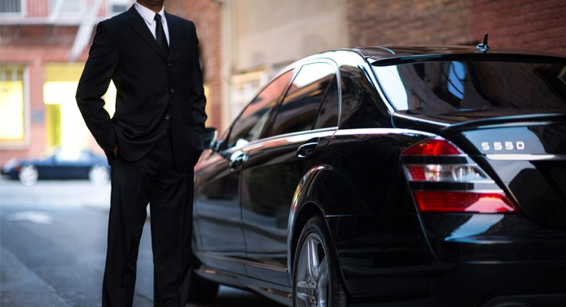 man in black suit near black car