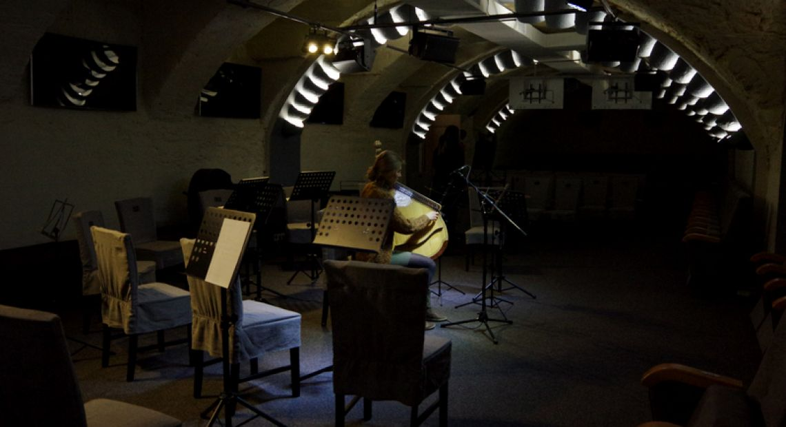 musician playing on string instrument in dark concert hall with chairs