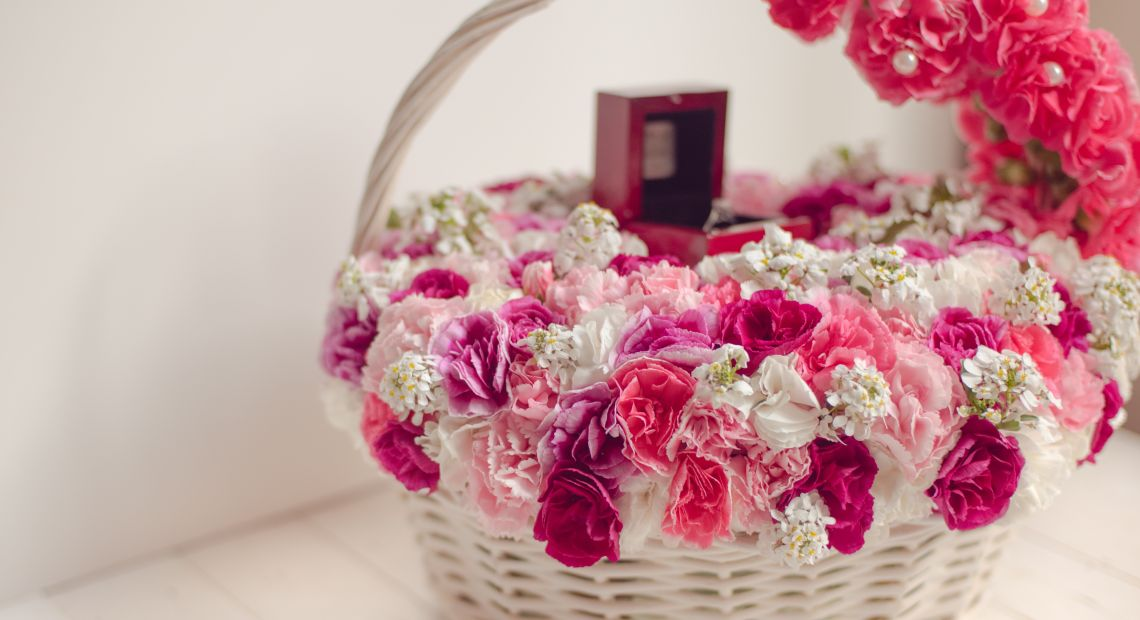 white basket with pink and white flowers and small gift box