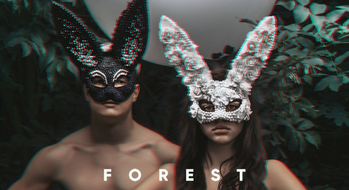 A couple wearing masks in a forest