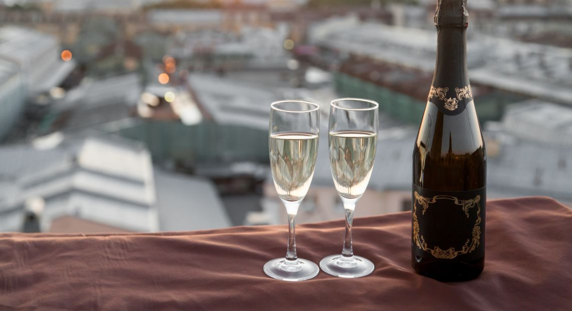A bottle of champagne with two glasses on a rooftop