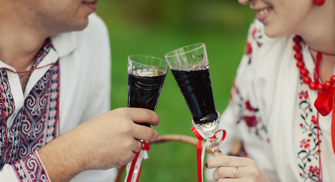 Couple sharing a glass of nalyvka on a picnic