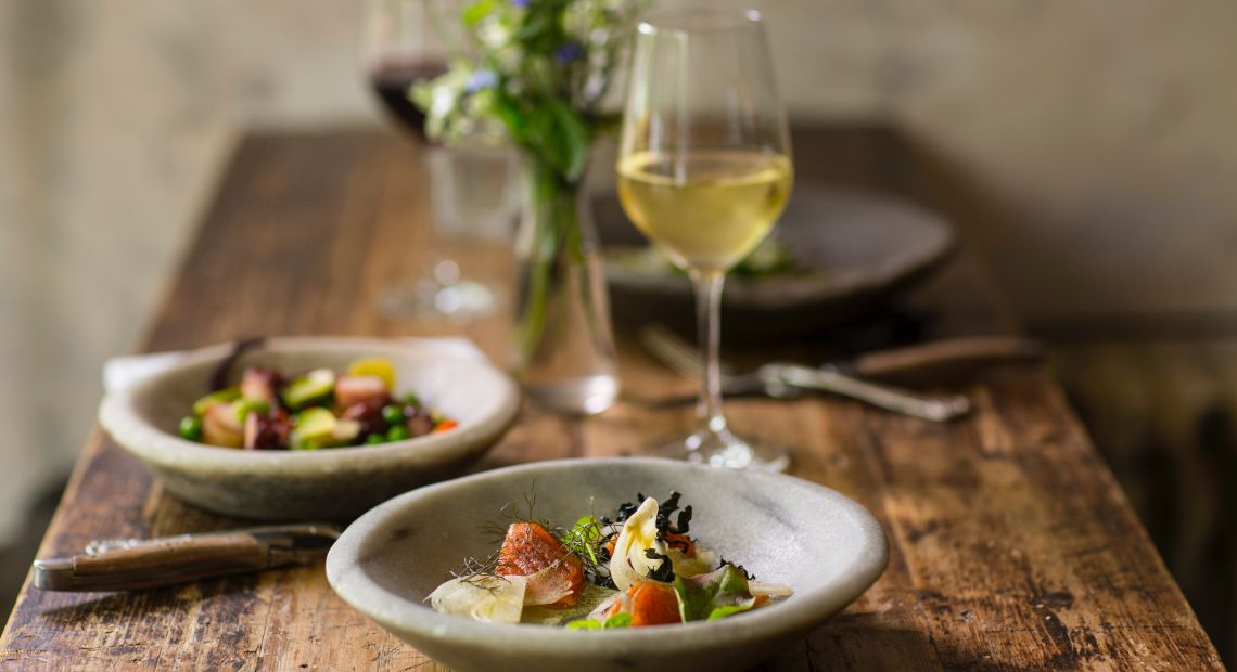 Delicious food on a stylish plate and white wine