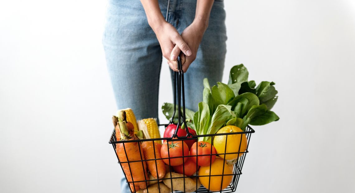 Woman holding a basket with vegetables