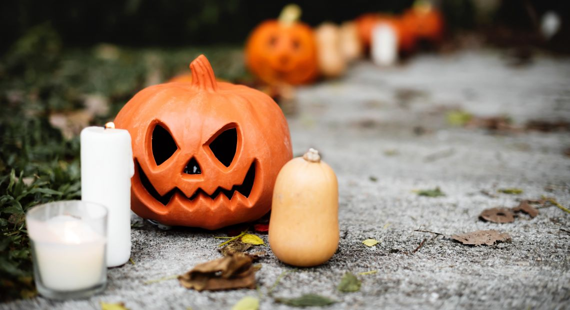 Jack-o-lantern and candles on the ground