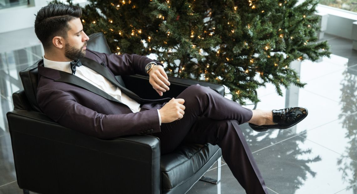 Man in a suit sitting by the Christmas tree