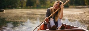 girl in boat with paddles on lake