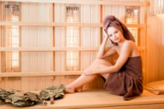 young girl wrapped in brown towel relaxing in sauna