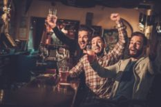 three men drinking beer and having fun in pub