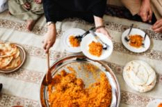 female hands stirring rice and putting it on plates on served table with plate with flatbreads
