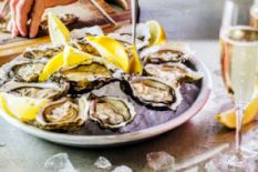 hand on table near plate with oysters served with lemon and glass of sparkling wine