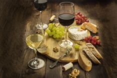 three glasses of wine, bread, cheese, nuts and grapes