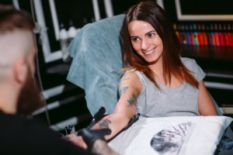 tattoo artist making a tattoo on smiling girl`s hand in salon