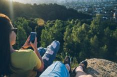 two people sitting on mountain with smart phone