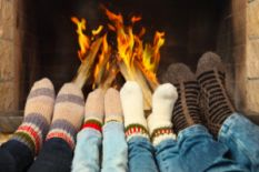 four pairs of legs in socks in front of fireplace
