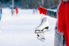 Person in red mittens holding ice skates