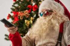 santa claus in colorful glasses with remote near christmas tree