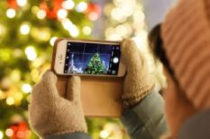 Person holding a phone and taking a pic of a Christmas tree
