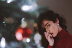 Girl standing by the Christmas tree