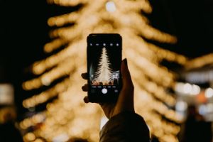 hand holding smartphone taking a photo of christmas tree