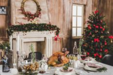 festive Christmas table with dinner near decorated fireplace and Christmas tree