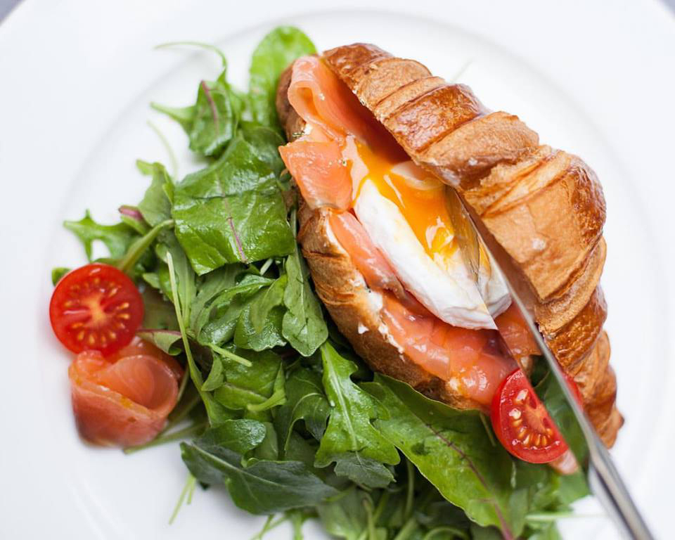 croissant with salmon, salad and egg