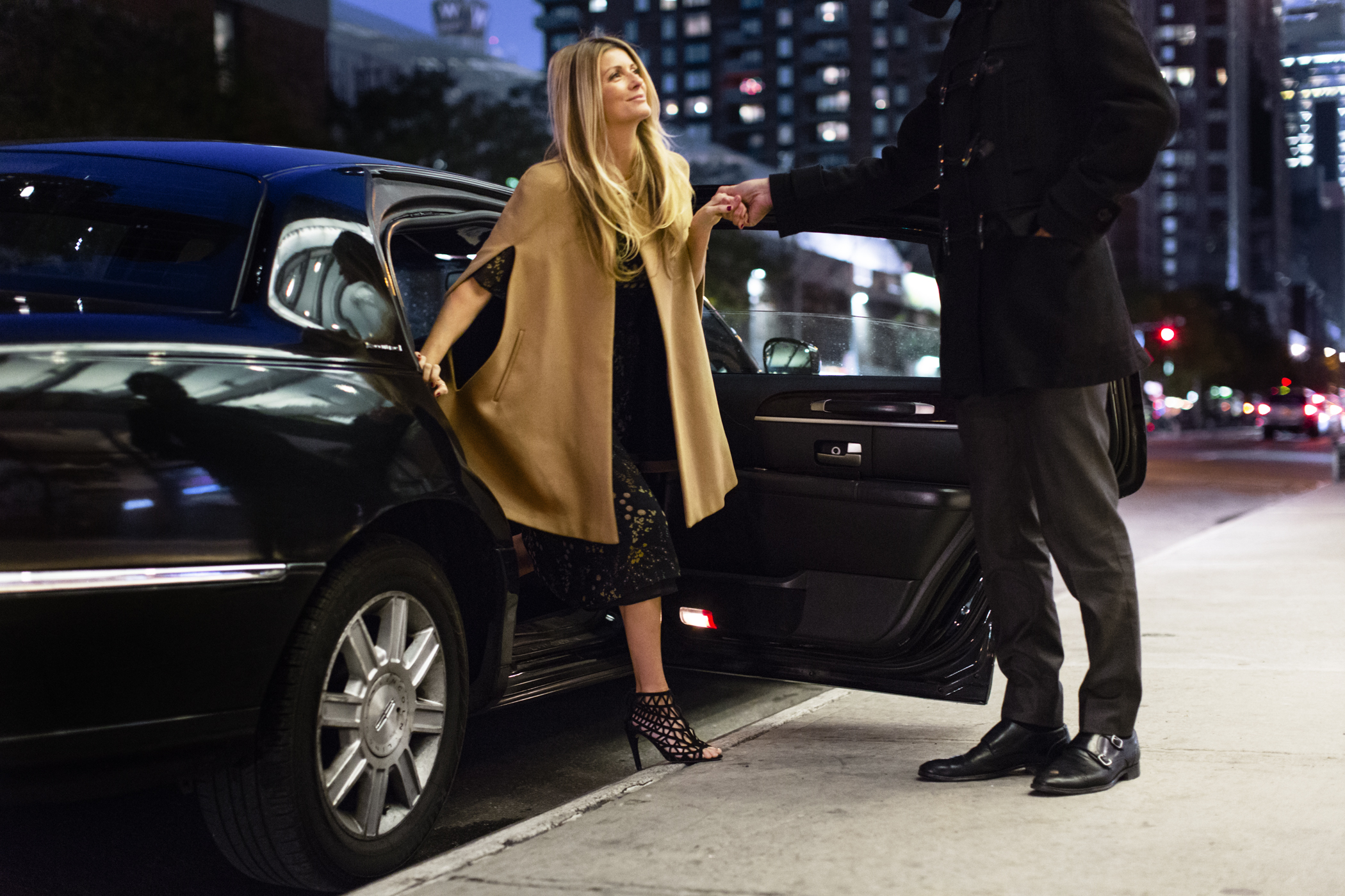 man helping woman in stylish clothes to get out of black car