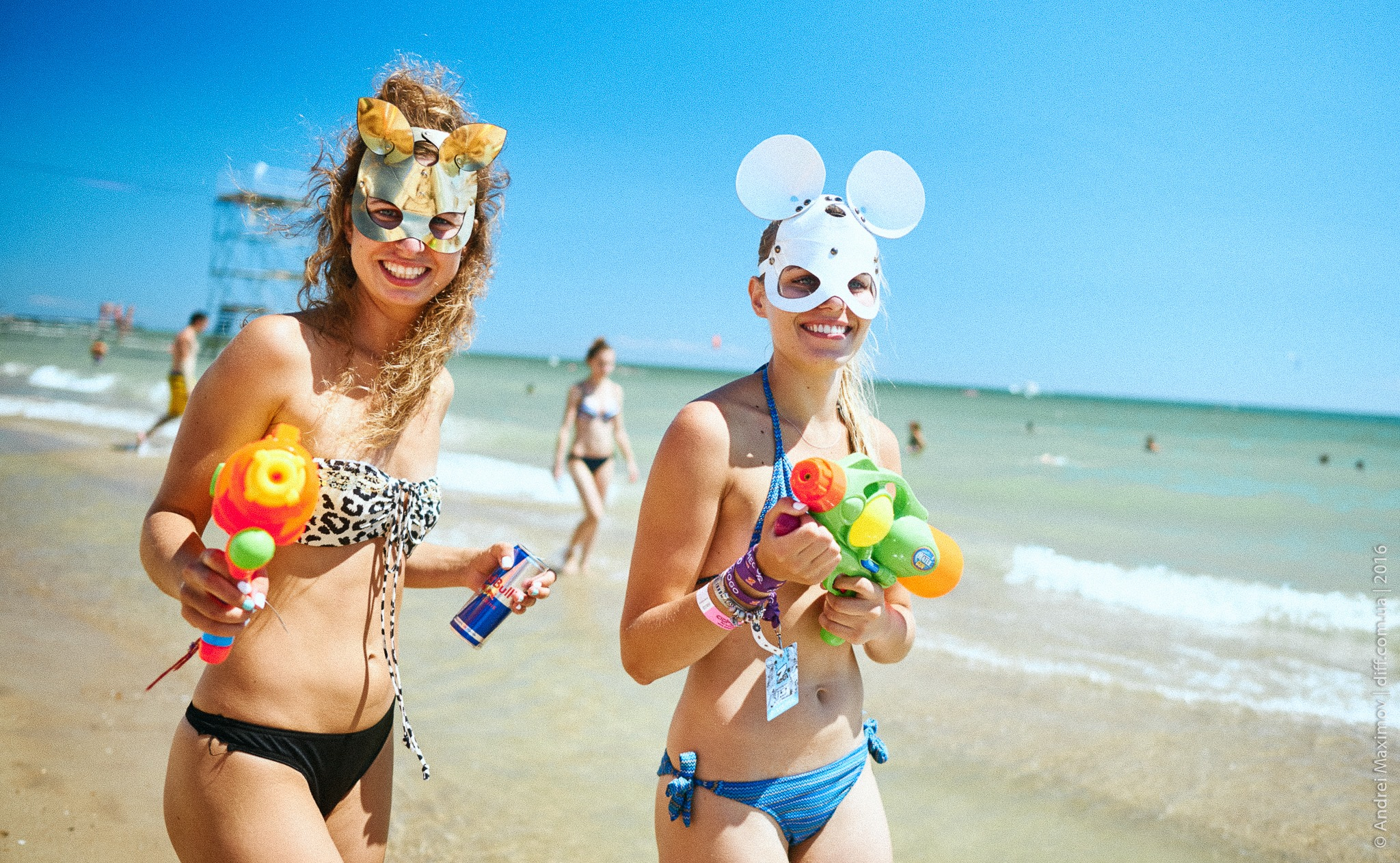 two girls in swimming suits on seashore in masks holding water pistols