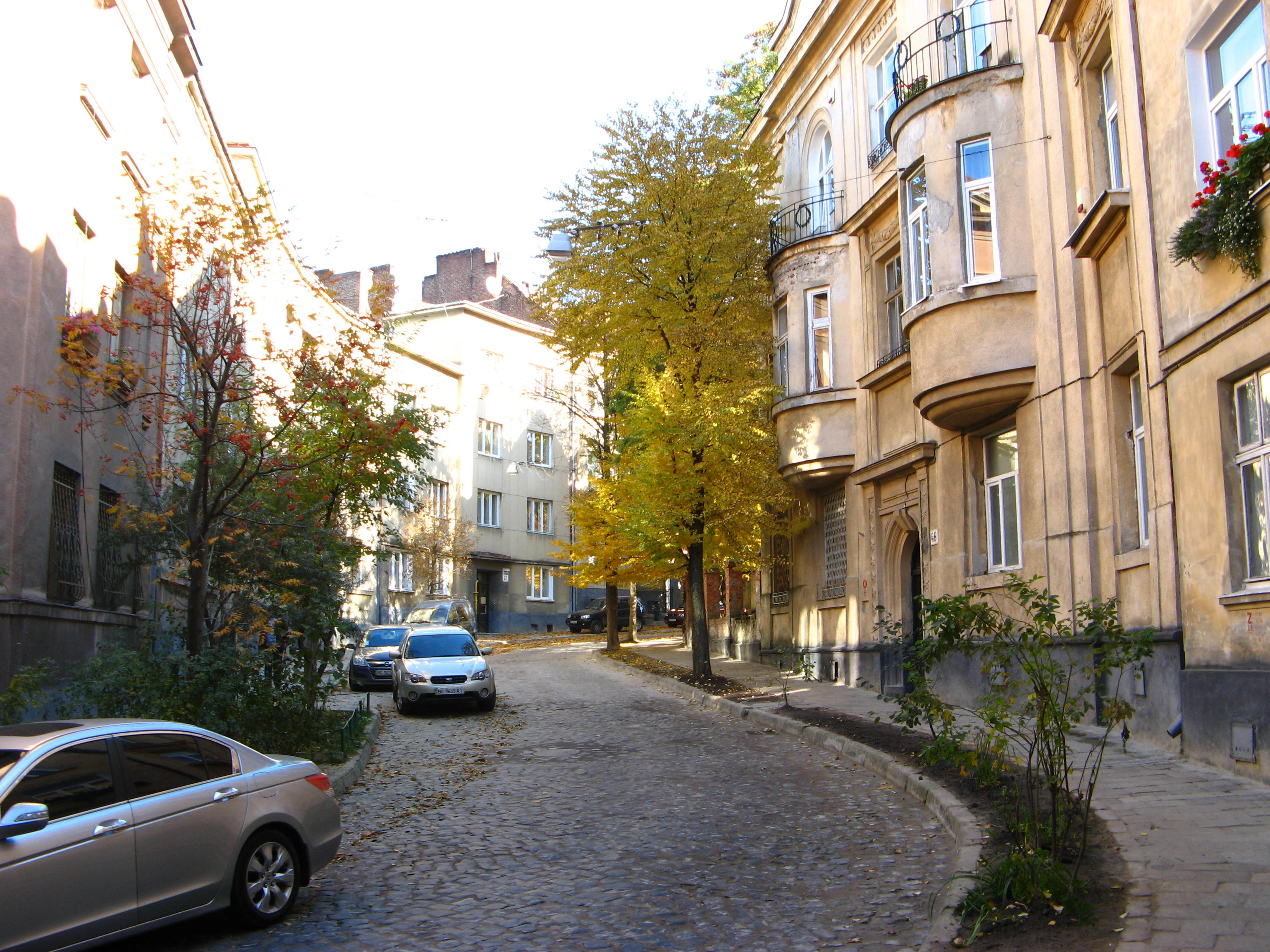 narrow street with buikdings and cars