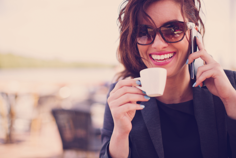 woman holding coffee cup and talking on mobile phone