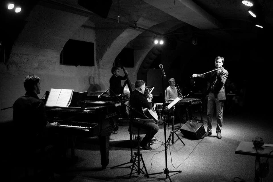 white and black picture of musicians playing piano, violin, guitar and bass in dark concert hall