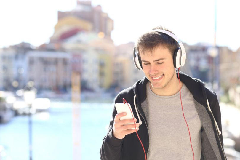 young man in street with smartphone in headphones