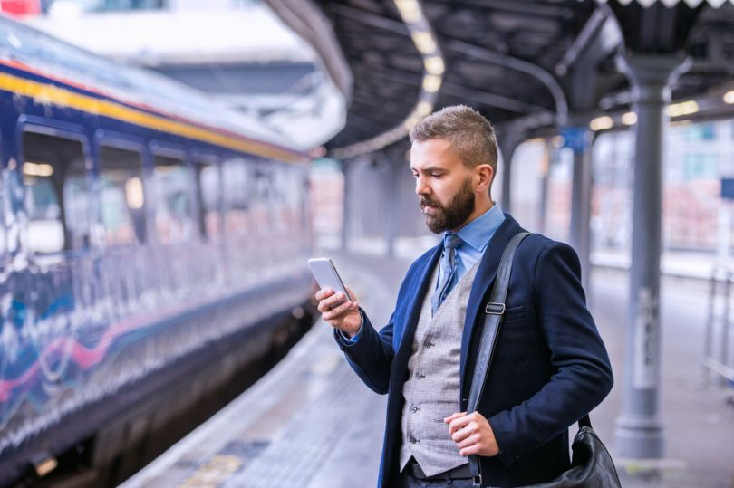 man with smartphone on train station