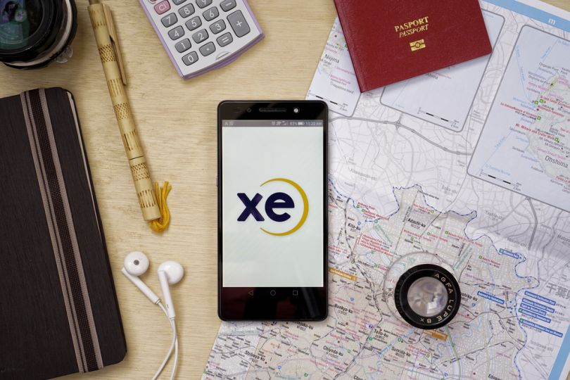 passport, map, caluclator, headphones and smartphone with open XE app