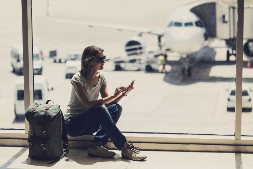 girl in the airport looking in smartphone