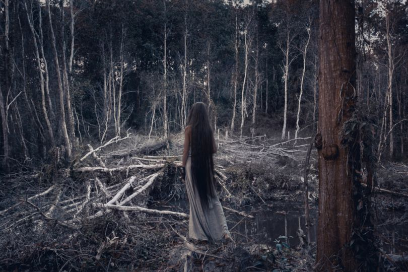 girl with long hair in creepy forest