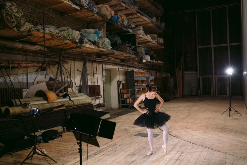 Ballerina stretching behind the scenes of the theatre