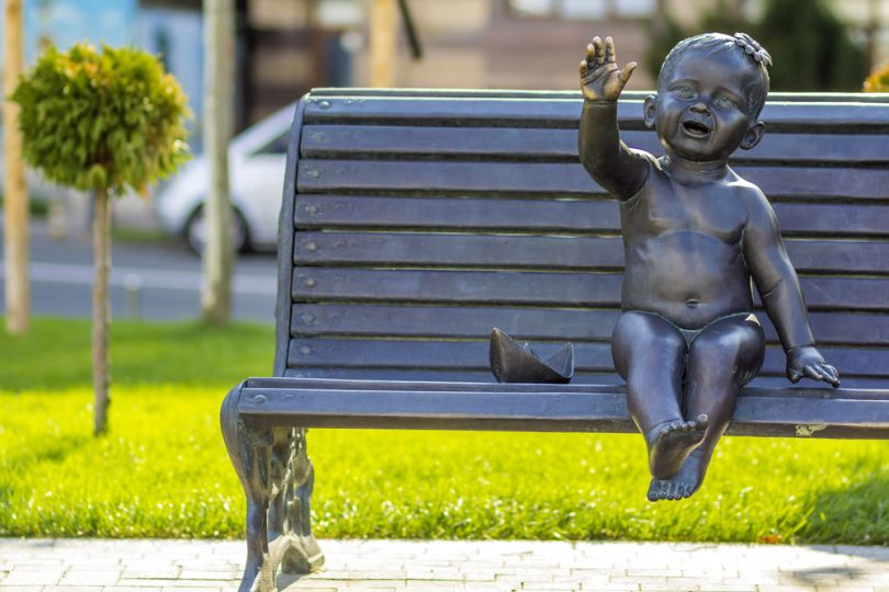 Sculpture of a kid on the bench in Kyiv