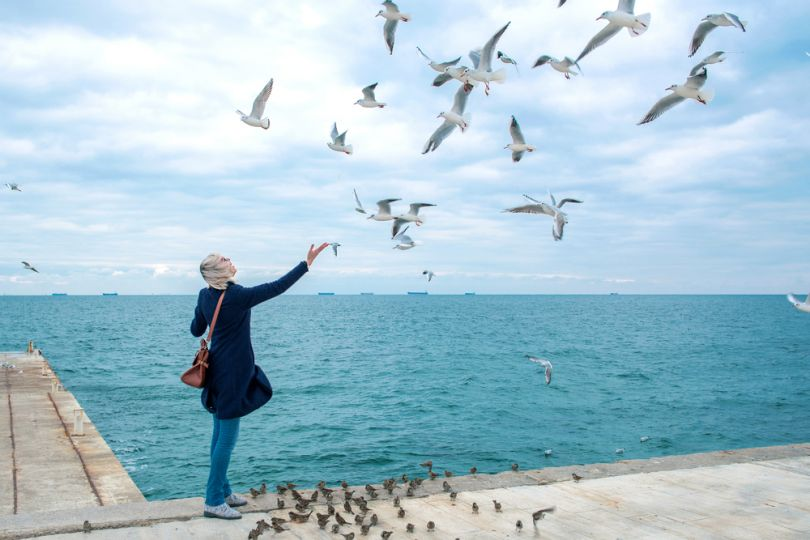 Woman feeding birds on a beach in Odesa