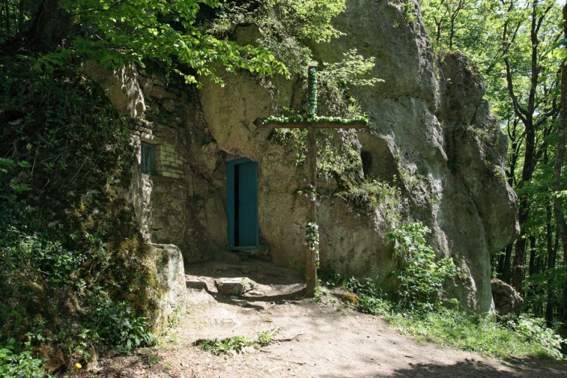 cave in rocks with cross on entrance