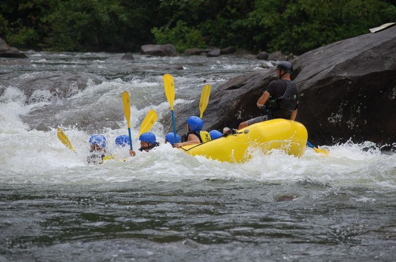 people doing rafting on mountain river