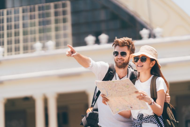 man explaining way to female tourist with map