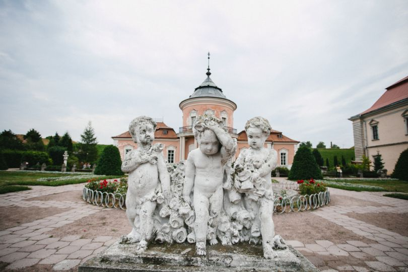statue of three cupids with castle on background