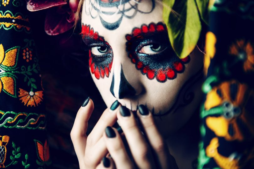 Girl in traditional Mexican Day of the Dead makeup