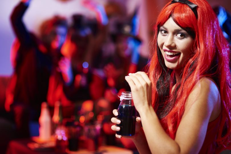 Girl in a red wig with a cocktail