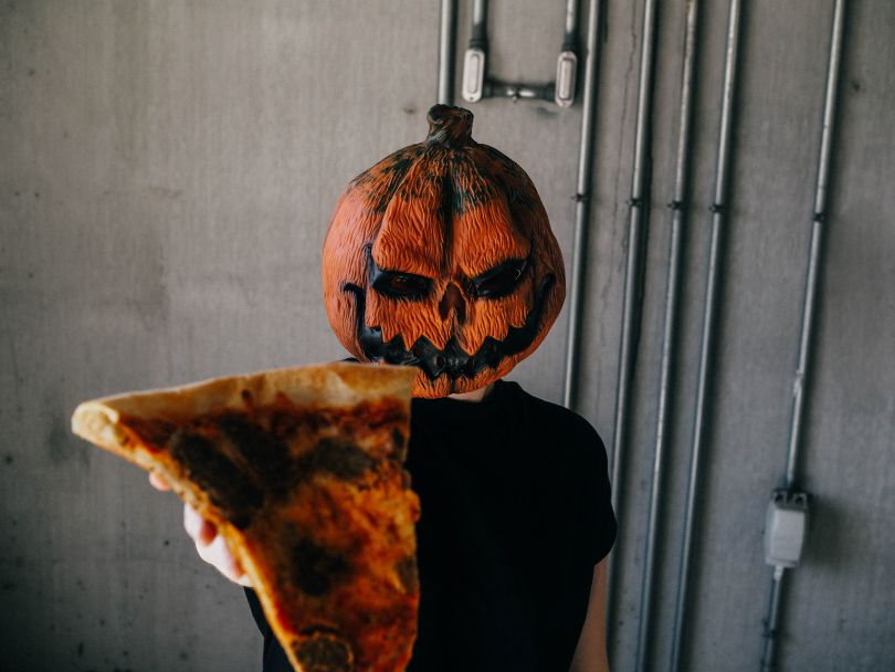 Man with a pumpkin Halloween costume holding a pizza slice