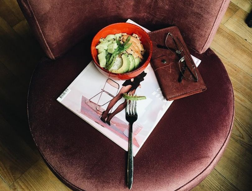 glasses, magazine and dish with salad on table