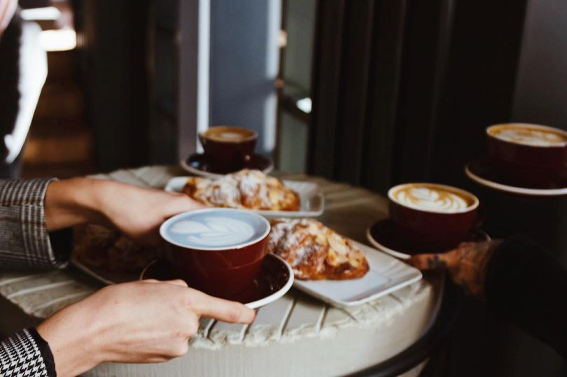 hands on table with bread and coffee