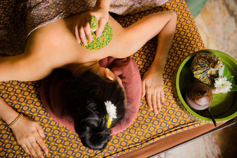 Woman receiving traditional herbal compress treatment