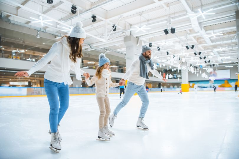 A family skating in an indoors rink